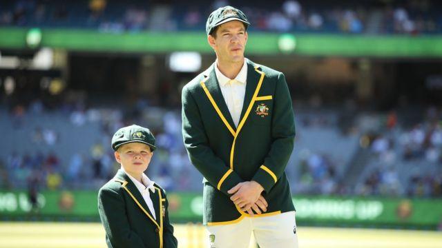 Archie Schiller in the full Australian team Test uniform stands next to cricket captain Tim Paine