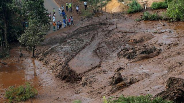 Pessoas observam lama em região onde barragem se rompeu em MG