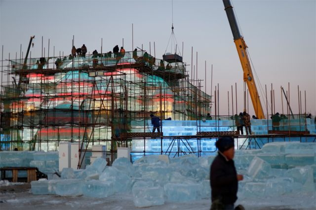 Workers on scaffolding build an ice structure at the site of the Harbin International Ice and Snow Festival