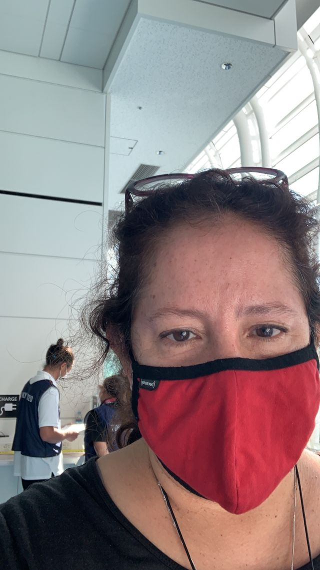 Lourdes arrives at the airport, wearing a mask