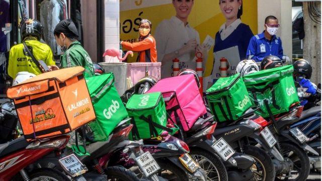 Tài xế giao thức ăn đứng chờ bên ngoài một nhà hàng hiện giờ chỉ được bán món ăn mang đi tại Bangkok