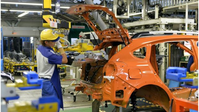 スバルの工場でバッテリーを搭載する作業員