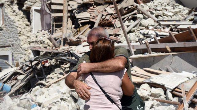 Hombre y mujer abrazados frente a escombros
