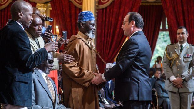 法国总统奥朗德(中右)和一名老兵握手