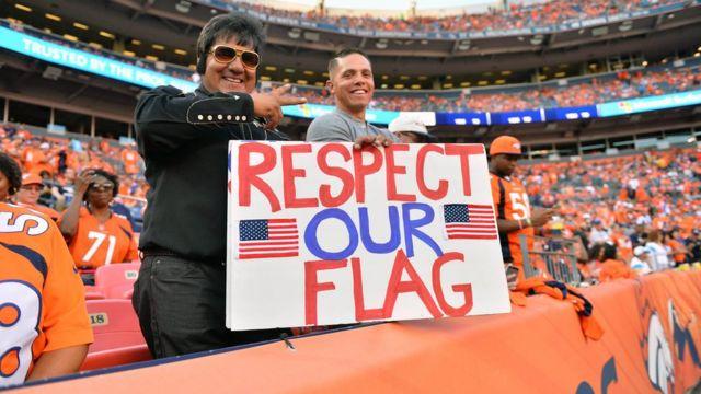 """Cartaz """"Respeite nossa bandeira"""", exibido em partida de futebol americano"""
