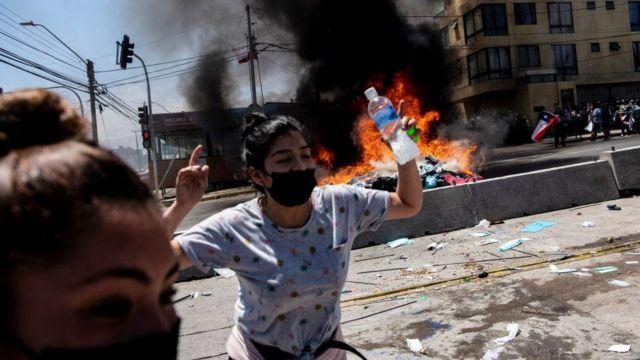 Mujer celebra la quema de ropa de los migrantes