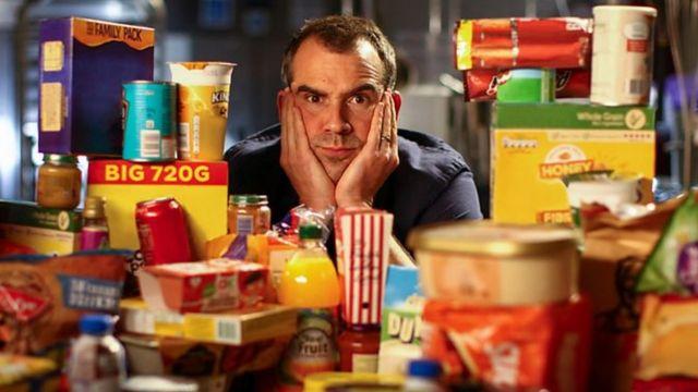 Chris Van Tulleken sentado entre uma montanha de alimentos altamente processados