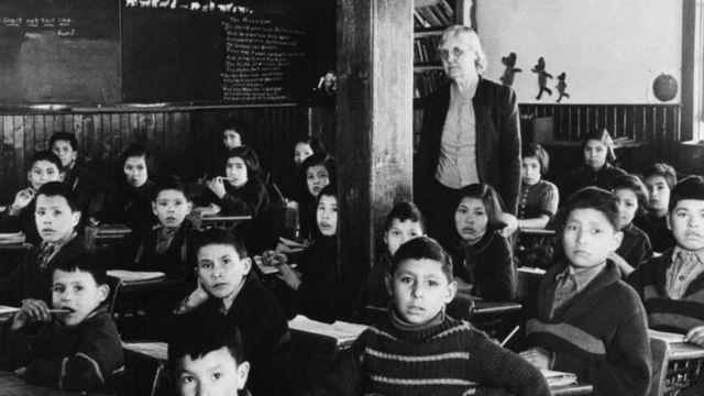 Crianças indígenas sentadas em sala de aula, com instrutora em pé; a foto é preto e branca