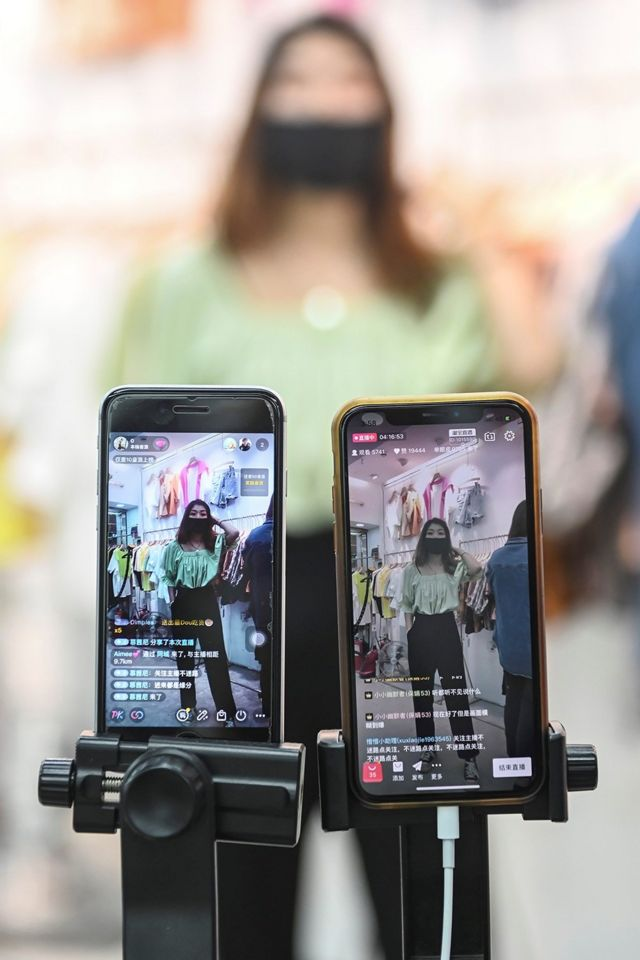 An anchor of a clothing store in Guangzhou is selling merchandise through live streaming.