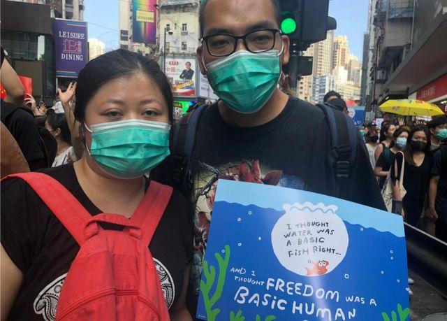 """34歲的Lisa與丈夫Tony手持標語,寫上""""水是基本魚權,自由是基本人權""""。"""
