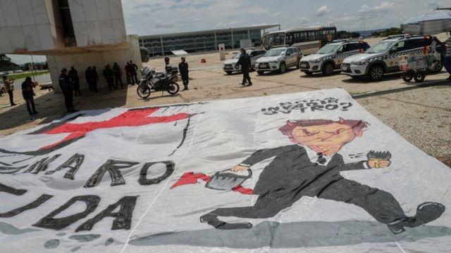 Bandeira com desenho de Bolsonaro ao lado de suástica nazista