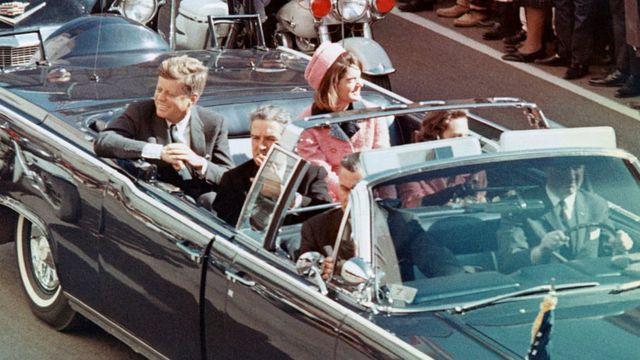 Kennedy e a mulher, Jacqueline, sorriem para a multidão que acompanhava o desfile em carro aberto