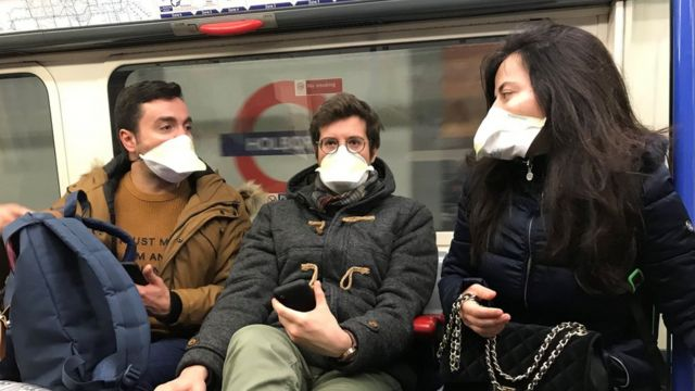 People wearing face masks on the London Underground, as the first case of coronavirus has been confirmed in Wales and two more were identified in England - bringing the total number in the UK to 19