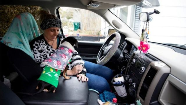Laramie White, whose home was among the thousands in the city that were left without power after extremely cold weather moved through Texas earlier in the week, stays warm with her dogs in her truck in Corpus Christi, Texas, U.S. February 16, 2021
