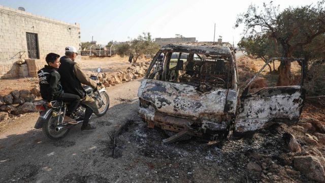 сирийцы на мотоцикле проезжают мимо обгоревшей машины