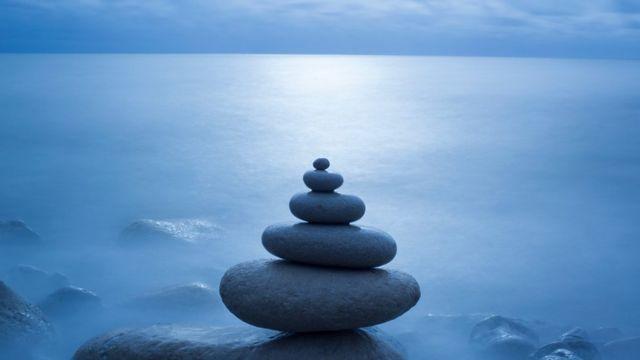 Una pila de piedras una sobre otra en delicado equilibrio frente al mar