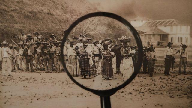 Lupa sobre foto histórica de escravos no Brasil. (Isabel Löfgren e Patricia Gouvêa/Modos de Olhar, série Mãe Preta/foto: Marc Ferrez)