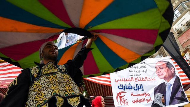 A whirling dervish dances past a poster of incumbent President Abdel Fattah al-Sisi wuth a caption reading in Arabic 'go and participate', outside a polling station in the capital Cairo's western Giza district on 28 March 2018.