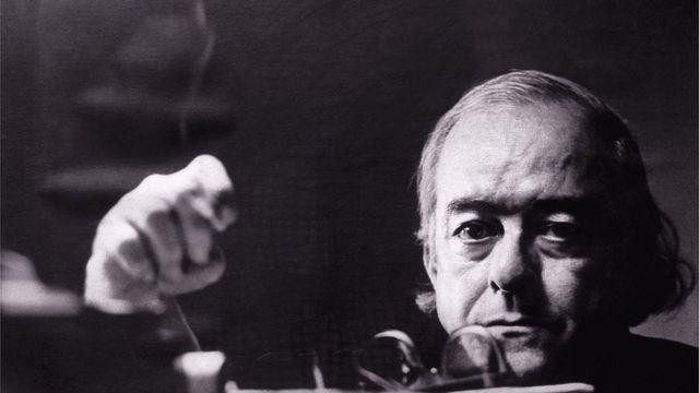 Vinicus de Moraes olha sério para foto em preto e branco, segurando um cigarro