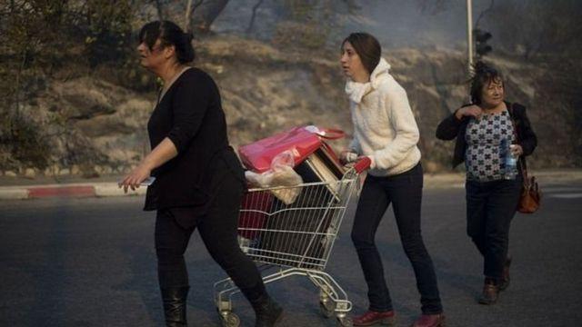आग के कारण घर छोड़कर जाते लोग