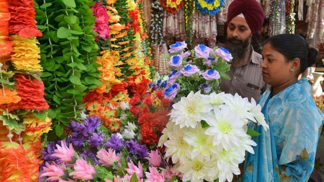 Sikh couple looks at artificial garlands ahead of Diwali in Amritsar