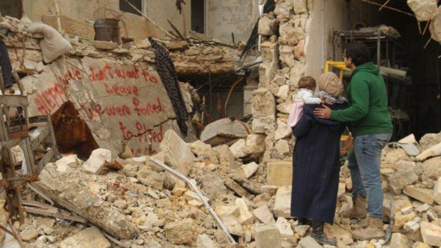 """La pareja está de pie frente a un grafiti que pintaron sobre unas ruinas y que dice: """"No queremos irnos, fuimos obligados a hacerlo""""."""