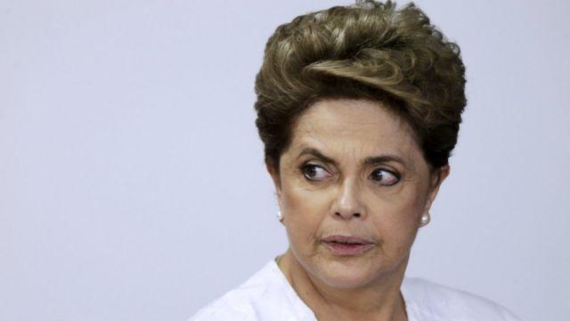 Dilma com olhar sério olhando para o lado, vestindo branco e em frente a painel branco