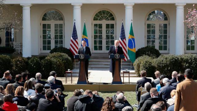 Bolsonaro e Trump no parlatório da Casa Branca, em foto de março, com bandeiras do Brasil e EUA atrás deles