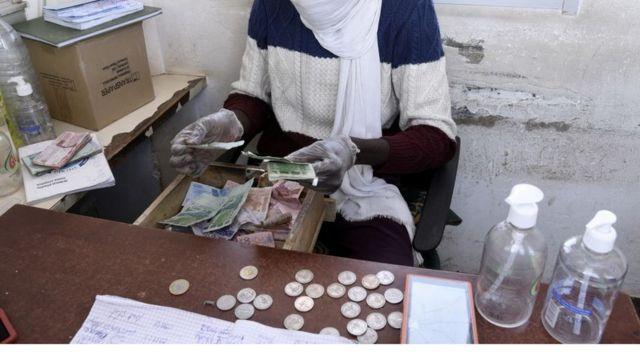 Un homme portant un masque en train de compter l'argent.