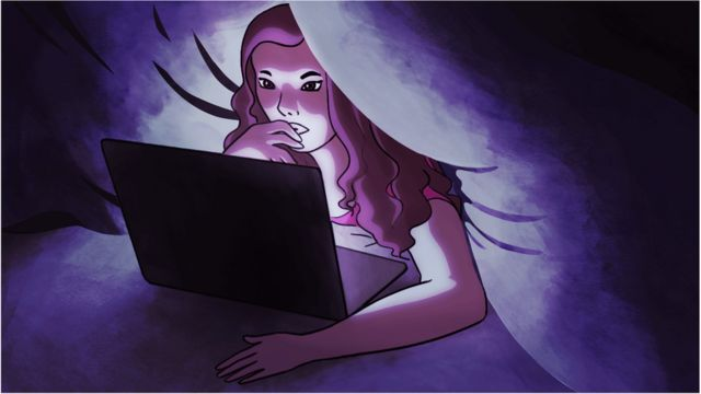 A woman looking at a laptop under the sheets
