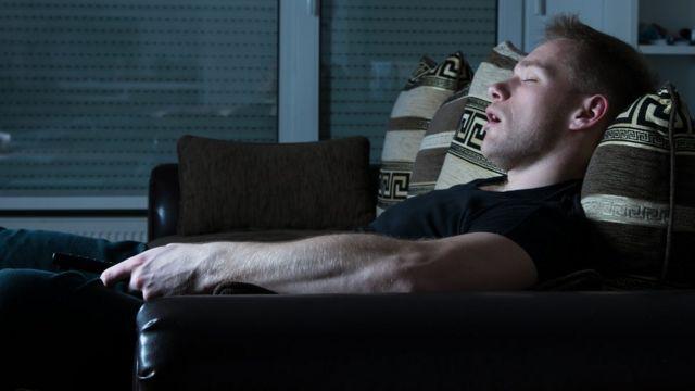 Un hombre duerme frente a un televisor encendido.