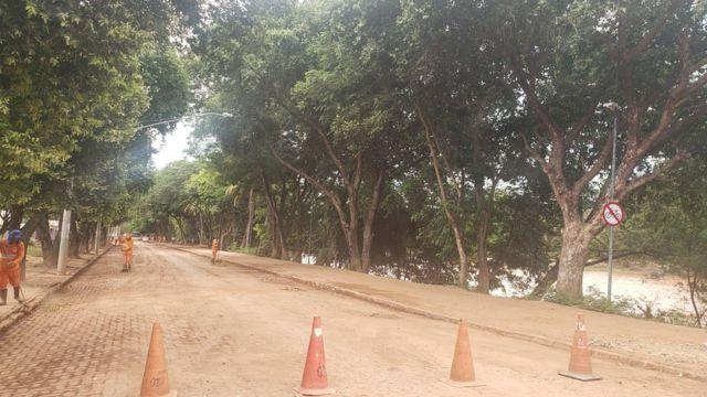Trabalhadores da prefeitura limpam a poeira e lama que se espalhou pelos bairros de Governador Valadares