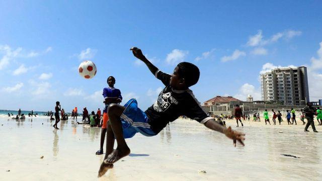 Boy playing football on the beach