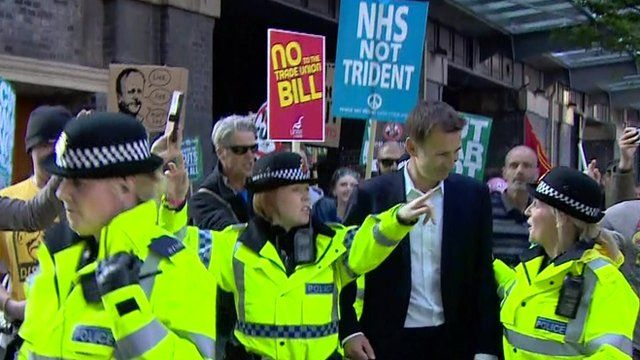 Jeremy Hunt with police officers and protesters