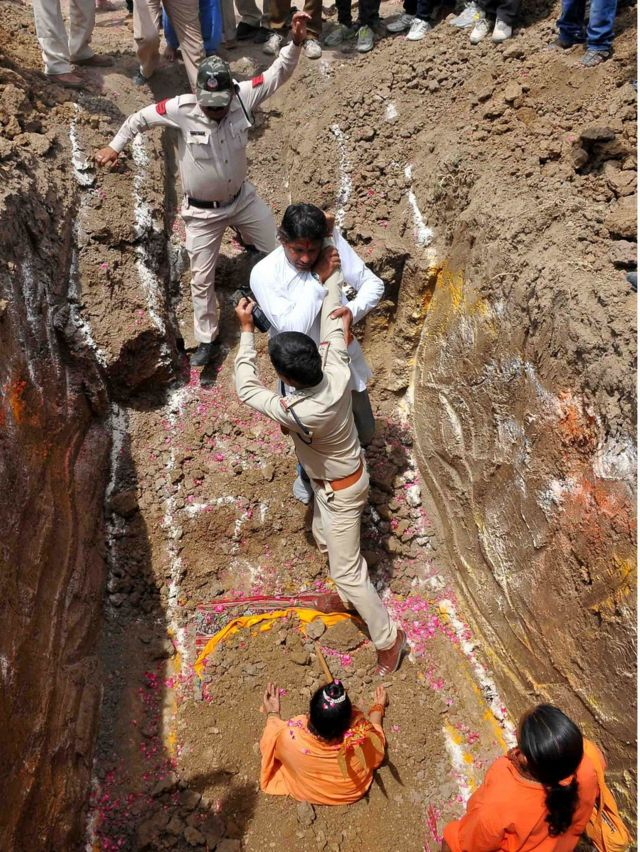 """A devotee of Indian Hindu Akhara leader Trikal Bhawanta grapples with two police officials in a deep grave, alongside the seated Trikal Bhawanta, as she undergoes a """"burial ritual"""" on 26 April 2016"""