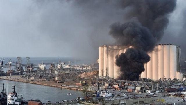 Destrozo y humareda en el puerto de Beirut donde ocurrió la explosión.