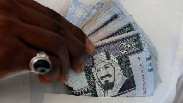 A Saudi man shows Saudi riyal banknotes at a money exchange, in Riyadh, Saudi Arabia (30 January 2016)