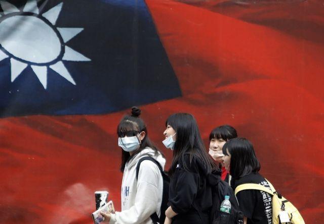 戴着口罩的台湾女生走过中华民国国旗(2021年4月11日资料照片)
