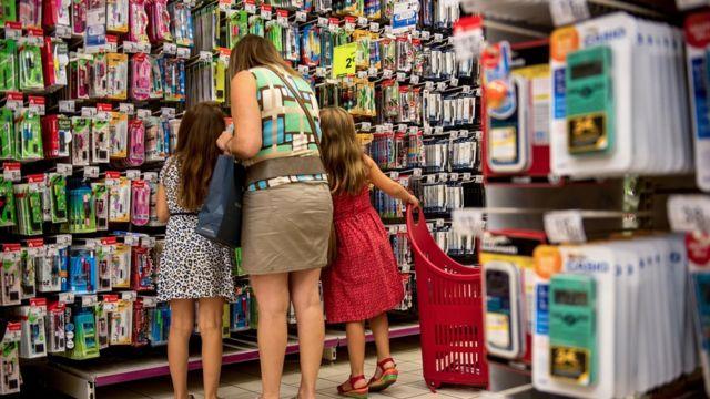 Una mujer con dos niños en una tienda.