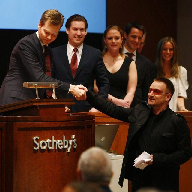 2008年,巴克的拍卖会为波诺(Bono)的艾滋病慈善基金会RED募集了4200万美元后,这名歌手握住他的手。巴克与赫斯特的合作从未间断 | Getty Images