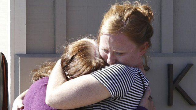Umpqua Community College alumnus Donice Smith (L) is embraced after she said one of her former teachers was shot dead.