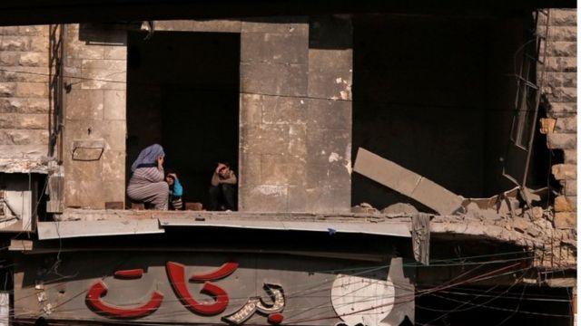 مدنيون يجلسون في منزل مدمر في حلب.