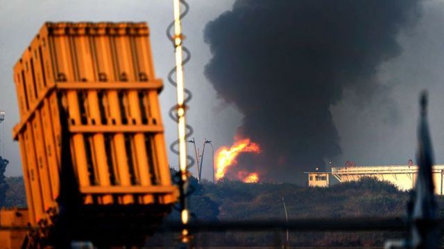 Une batterie du système de défense aérienne Iron Dome est visible au premier plan, tandis qu'un panache de fumée s'élève à l'arrière-plan.