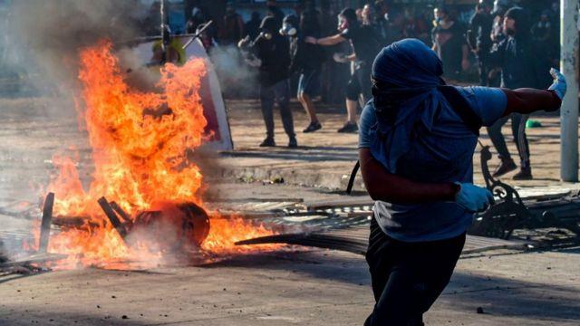 Manifestante devolviendo una bomba lacrimógena.