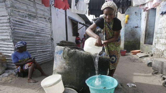 امرأة تحضر لغسل الملابس في أحد الأحياء الفقيرة في جنوب إفريقيا