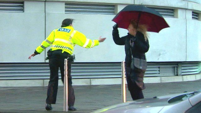 Woman being helped by female Police officer through gale.