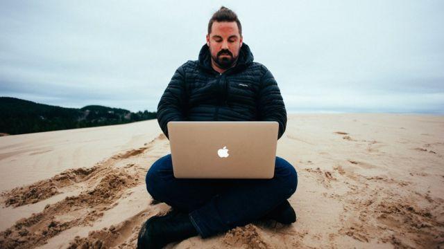 Grant Sabatier usando laptop na praia