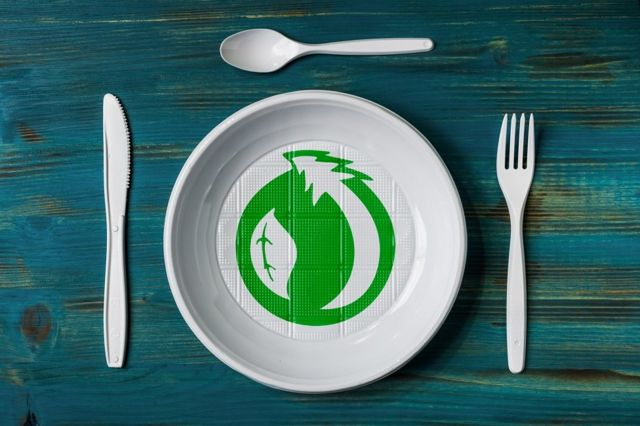 A plastic plate and cutlery with environmental green logo (stock photo)