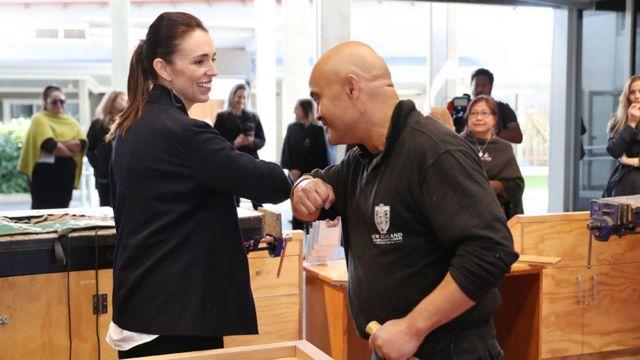 Ardern se saluda con el codo con un empleado del sector turístico