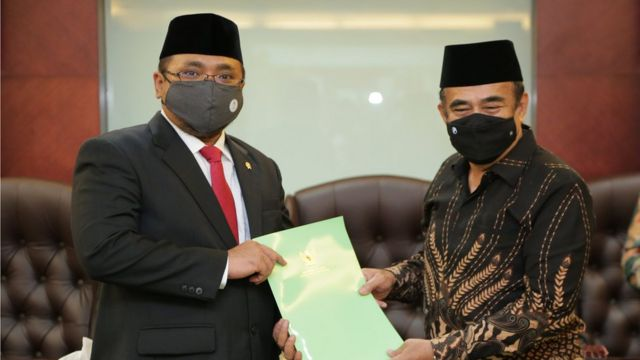 Menteri Agama Yaqut Cholil Qoumas (kiri) bertukar naskah dengan mantan Menteri Agama Fachrul Razi saat serah terima jabatan di Kantor Kemenag, Jakarta, Rabu (23/12)